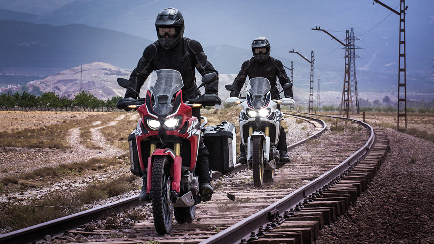 Two Honda Africa Twin motorcycles riding along train tracks