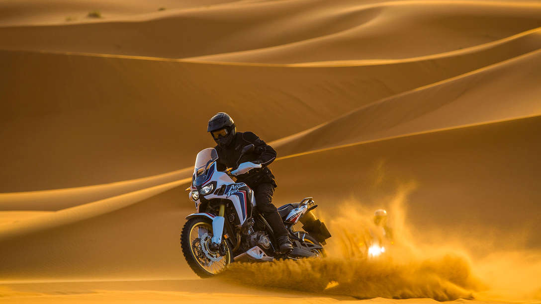 Africa Twin driving through desert sand