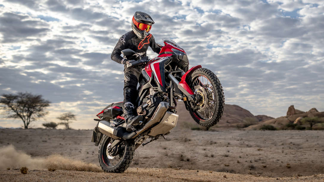 Honda Africa Twin, 3-quarter front right side, wheelieing in desert landscape