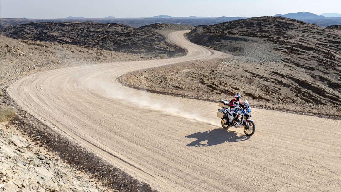 Honda Africa Twin Adventure Sports, 3-quarter front right side, riding on a dirt road through a desert landscape