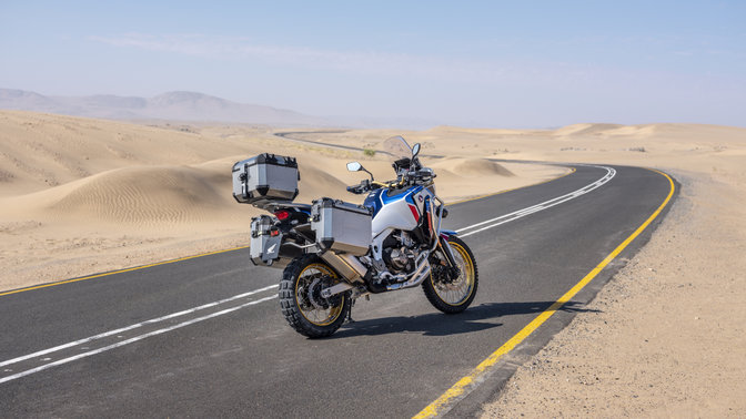 Honda Africa Twin Adventure Sports shot from above, 3-quarter front left side, riding on a road through a desert landscape