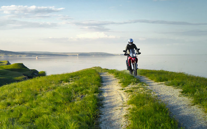 CRF250 Rally with rider on coastal road