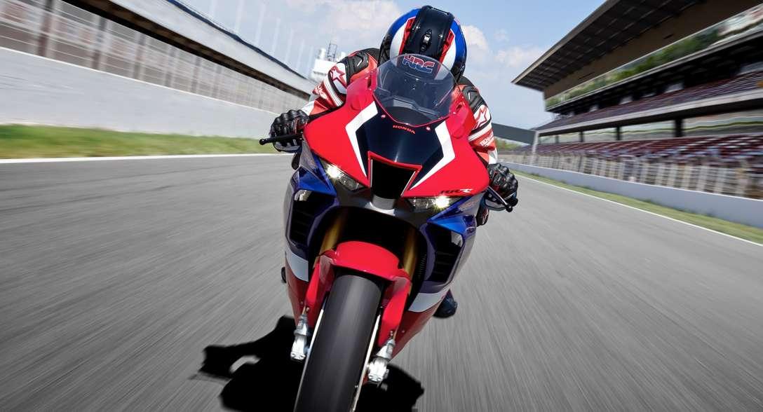 Honda CBR1000RR-R Fireblade SP, front face, with rider, riding on a racetrack