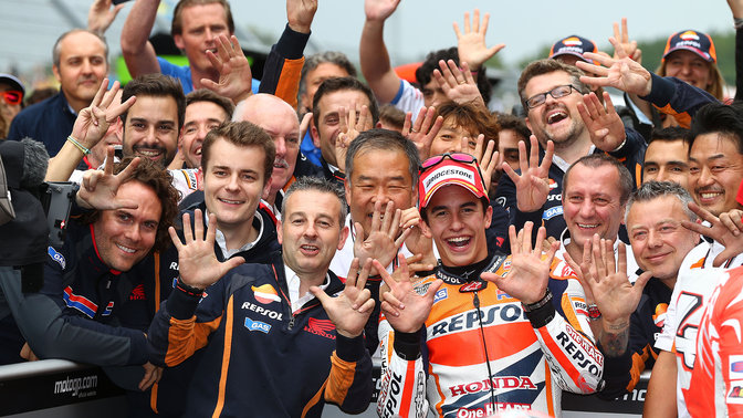 MotoGP racer celebrating a Honda win with crew.