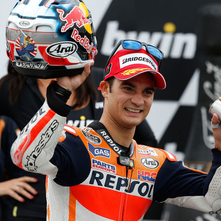 Rider on MotoGP podium with trophy.
