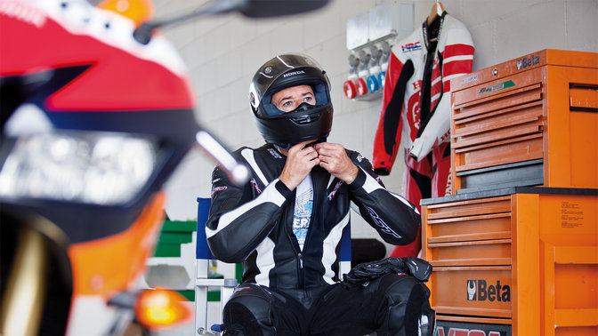 MotoGP rider in motorcycling gear and helmet.