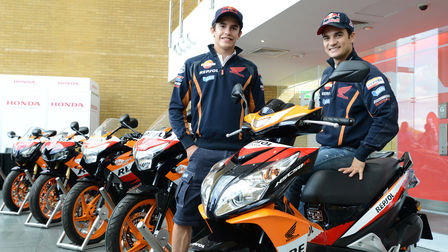 Two MotoGP racers with Honda motorcycles.