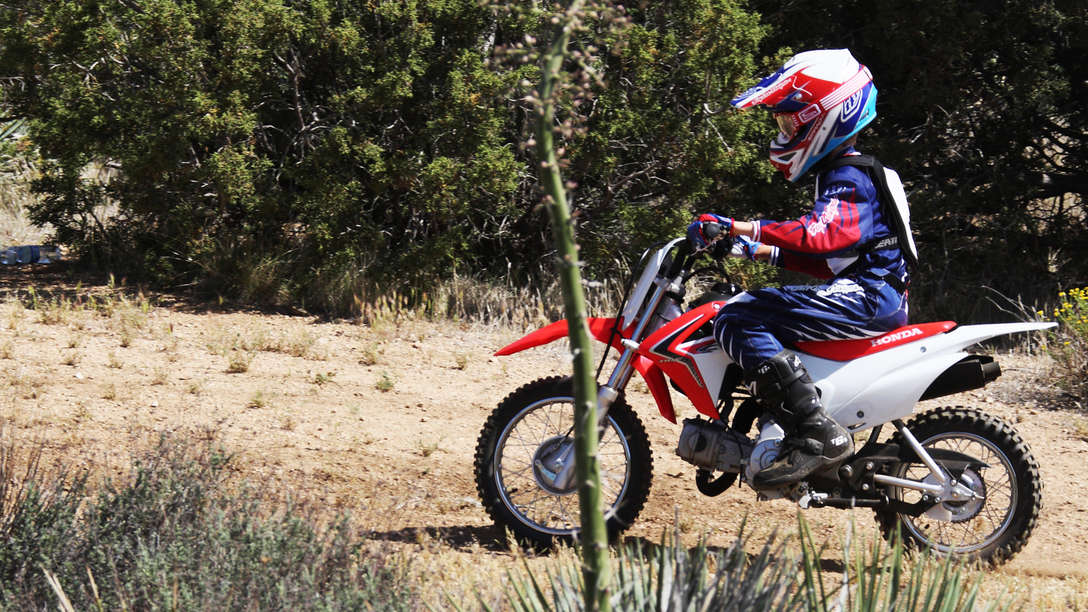 Side on, threequarter view of CRF110F with rider in dirt race location. Left facing.