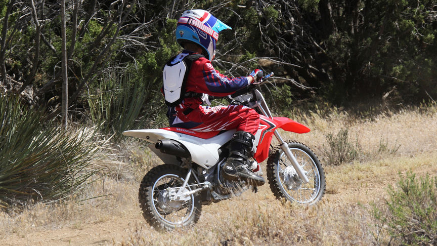 Front 3-quarter view of CRF110F with rider, off-road location.