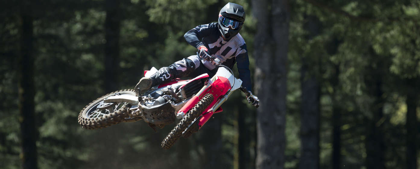 Front-facing CRF450R motorcycle jumping, with rider.