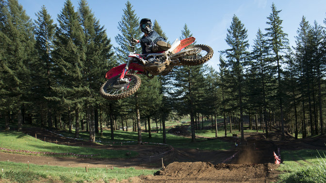 CRF450R jumping with rider. Dirt track location.