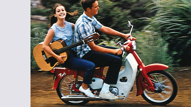 Honda cub with rider, and pillion carrying a guitar. Dirt road location. Right-facing.