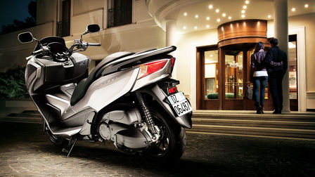 Rear 3-quarter view of left facing Forza 300, parked in front of hotel with rider and pillion going inside.