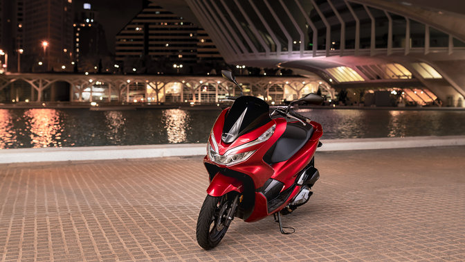 Front three quarters view of Honda PCX125 at a street location.