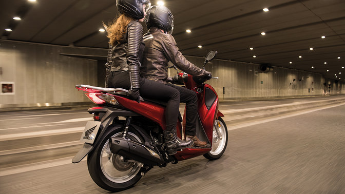 Side shot of 2 models on bike riding through a tunnel