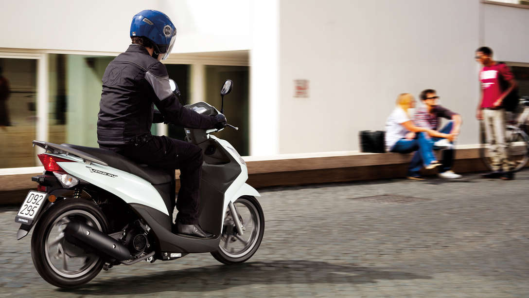 White Honda Vision 50 rear-threequarter view with rider. Right-facing (Road location).