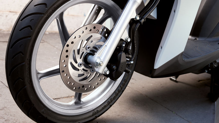 Honda Vision scooter front wheel focusing on CBS brakes. Left facing.