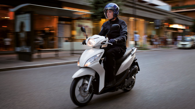 White Honda Vision scooter front-threequarter view with rider. Left-facing (Road location).