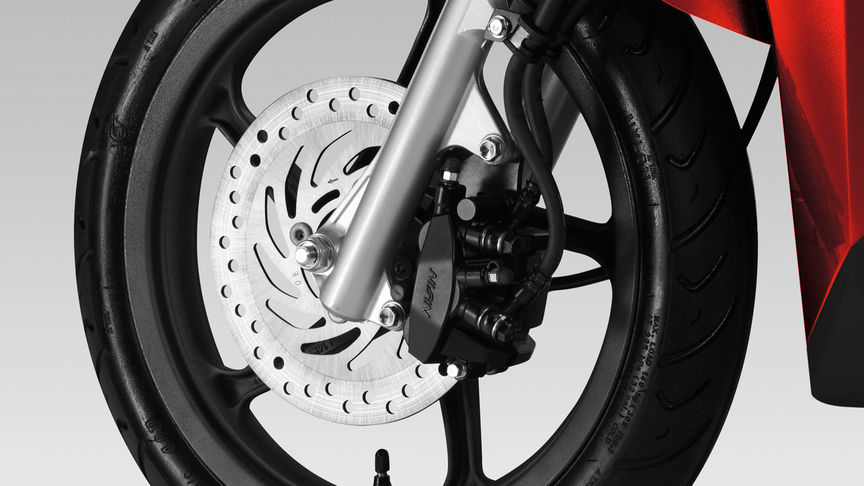 Honda Vision scooter front wheel focusing on CBS brakes.