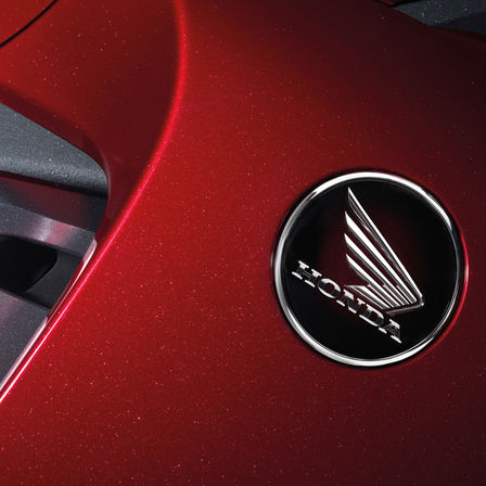 Honda Wing badge, on red motorcycle tank.
