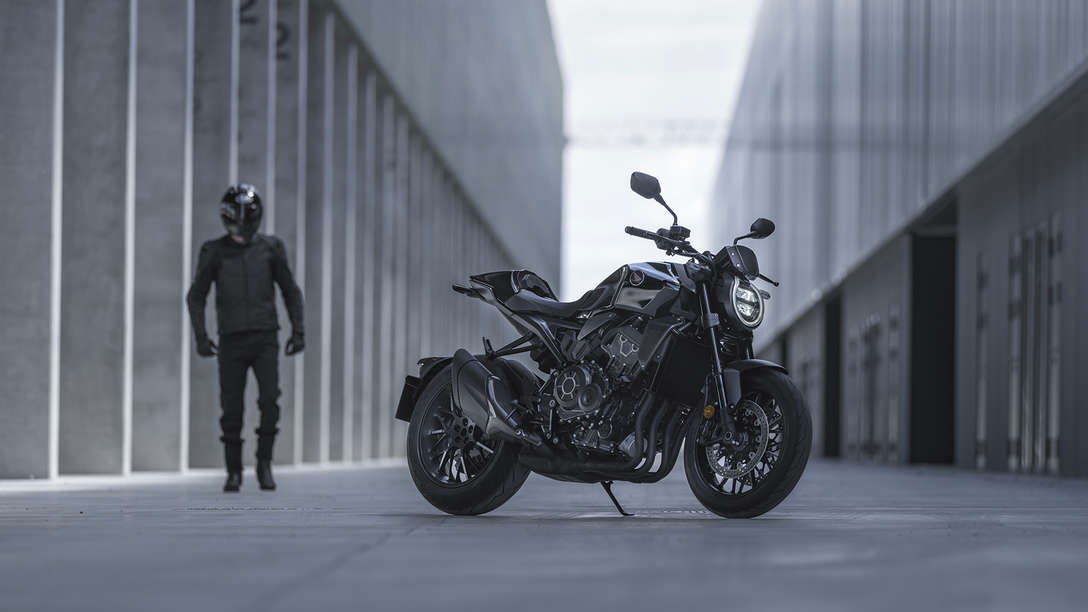 Honda CB1000R Black Edition - man standing next to the bike in the street between buildings