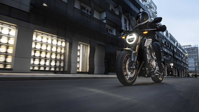 CB650R Neo Sports Café, 3-quarter left side with rider, in urban landscape