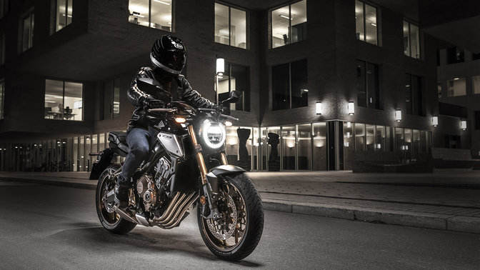 CB650R Neo Sports Café, 3-quarter front right side with rider, in urban landscape at night