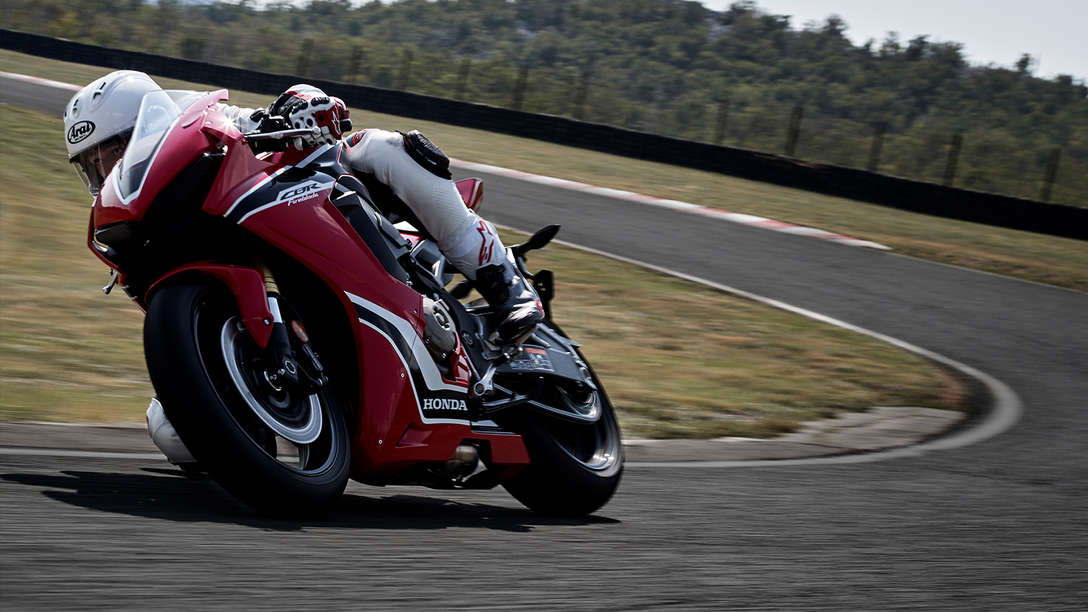 Front three-quarter facing Honda CBR100RR Fireblade with rider on race track.