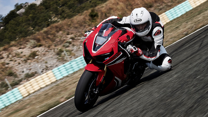 Front three-quarter facing Honda CBR1000RR with rider on track with knee down.
