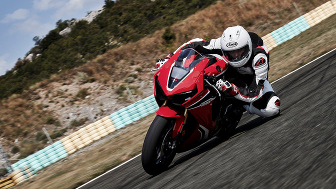 Front three-quarter facing Honda CBR1000RR with rider on race track.