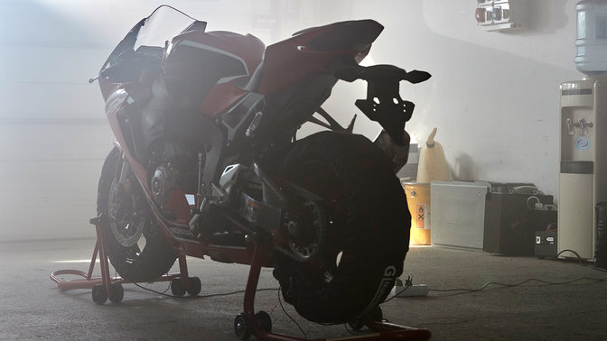 Rear three-quarter facing Honda CBR1000RR on stand in workshop.