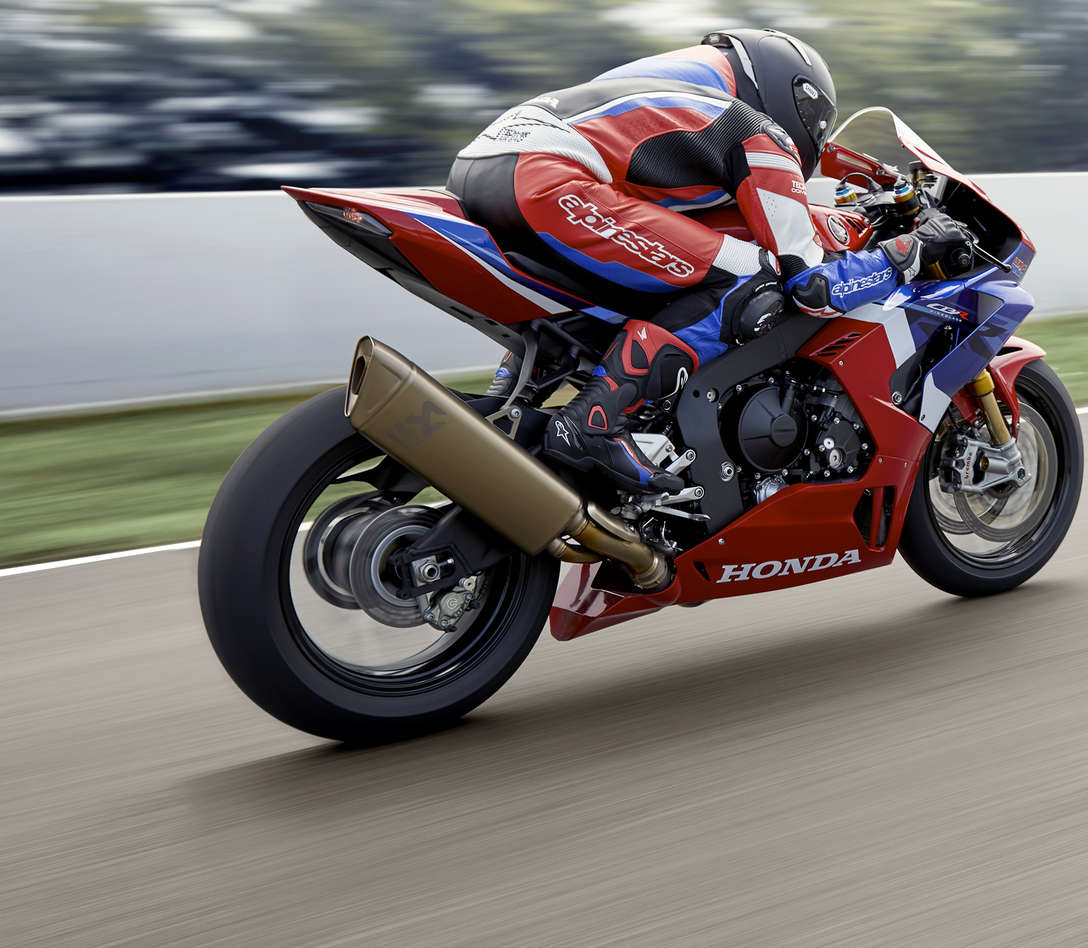Honda CBR1000RR-R Fireblade SP, quarter rear right side, with rider, rolling in a racetrack