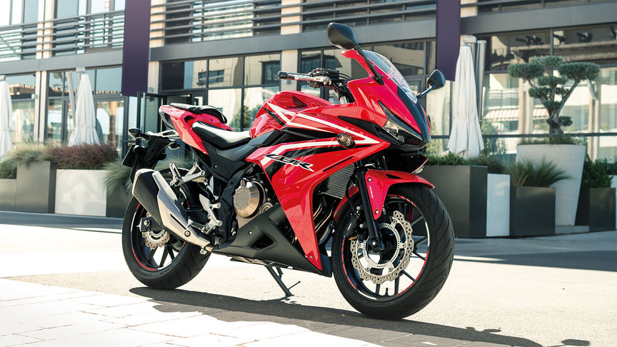 red CBR500R freestanding outside a glass window building