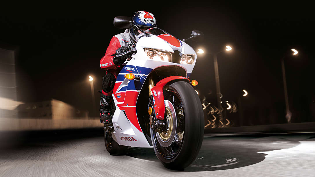 Honda CBR600RR motorbike front-threequarter view with rider. Right-facing (Road location).