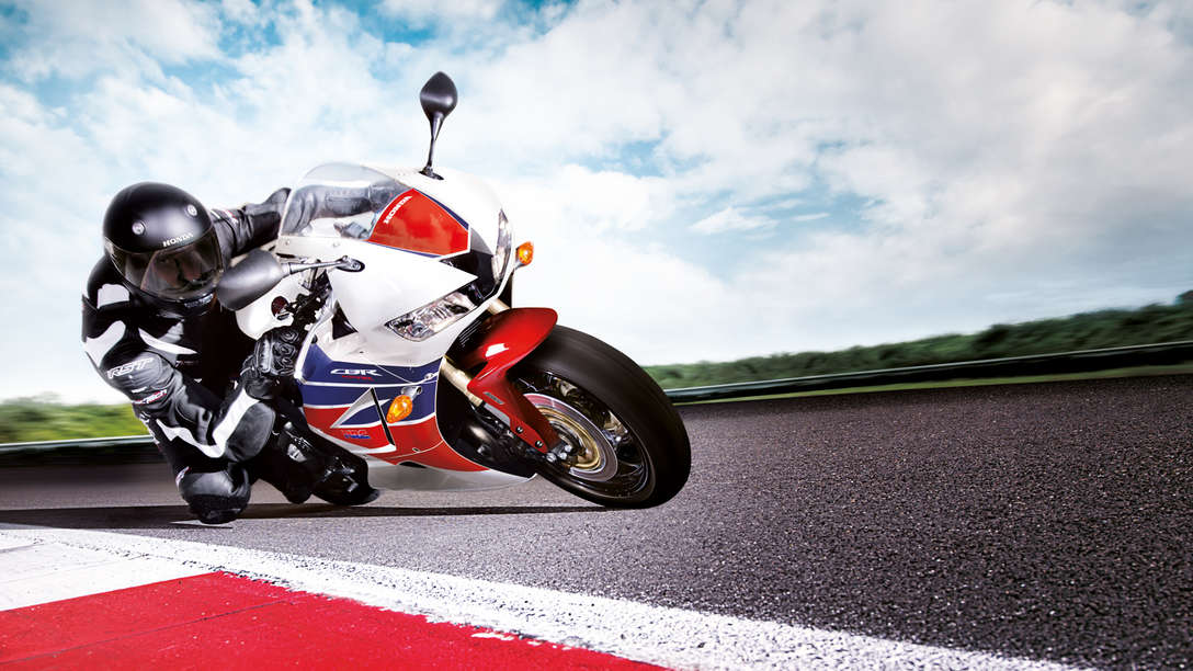 Honda CBR600RR motorbike front-threequarter view with rider, leaning into bend. Right-facing (Race track location).