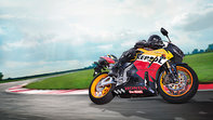 Honda CBR600RR Repsol-liveried motorbike front-threequarter view with rider, right-facing (Race track location).