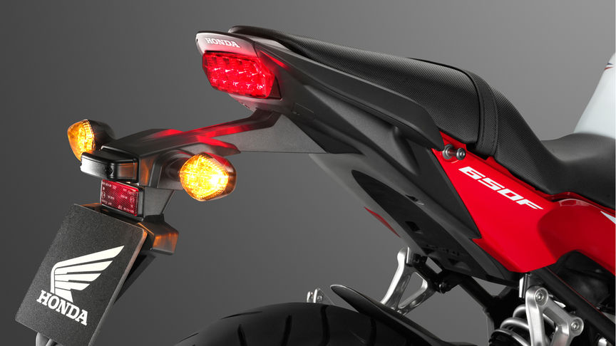 Close-up of front/side of SH Mode scooter, focusing on headlight, windscreen and handlebars.