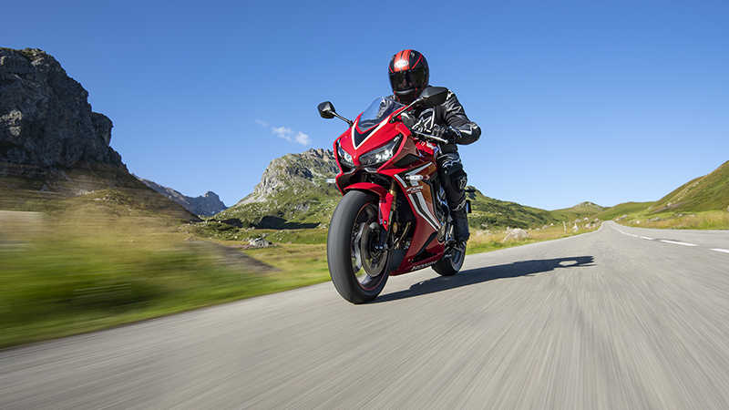 CBR650R, 3-quarter front left side, rolling with rider on a mountain road