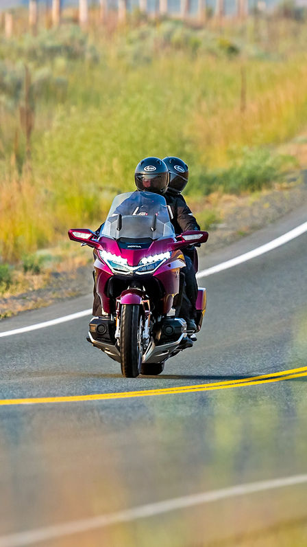 Front facing Honda Gold Wing on the open road.