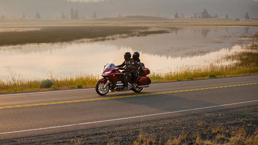 Rear three-quarter facing Honda Gold Wing on a mountain road.
