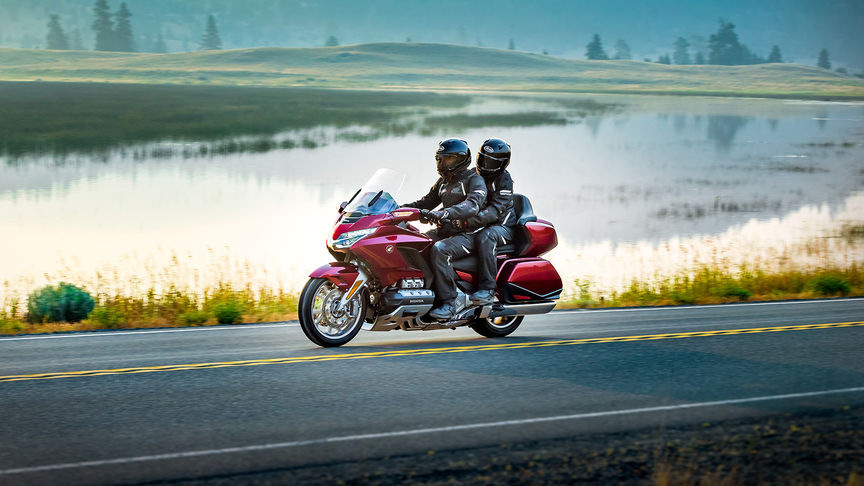 Front three-quarter facing Honda Gold Wing on a road next to a lake.