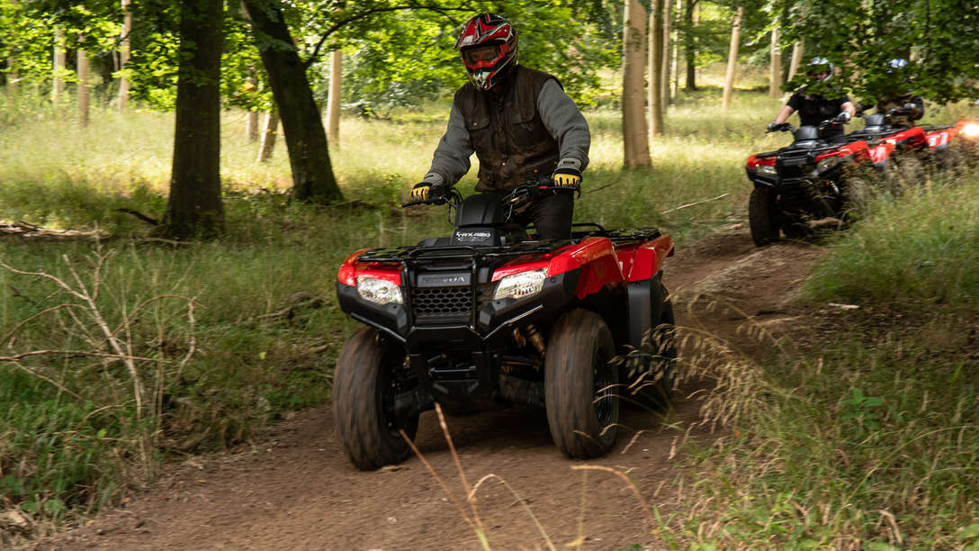 Front three-quarter, right facing Fourtrax 420, being used by model, field location.