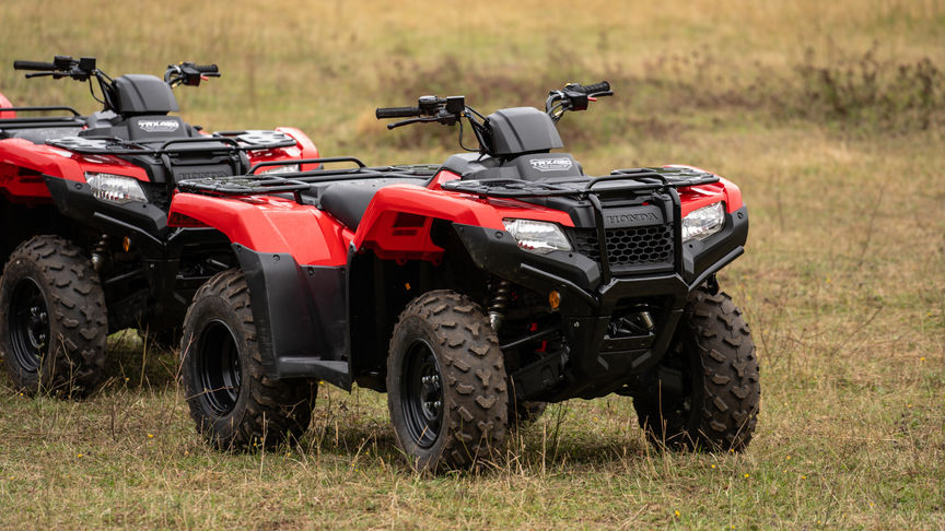 Front three-quarter, left facing Fourtrax 420, being used by model, field location.