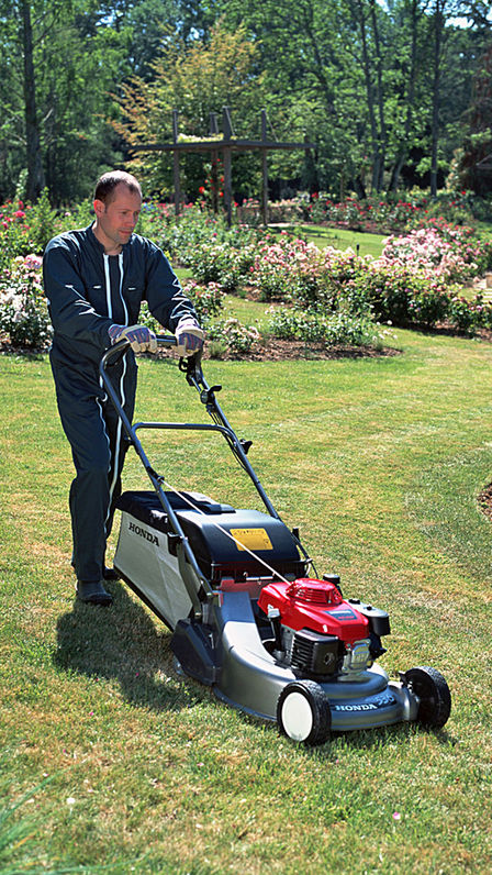 Lawnmower, front three-quarter, right facing, being used by model, garden location.