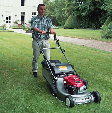 Front three-quarter lawnmower, being used by model, garden location.