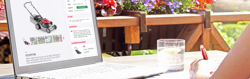 Desk in garden with laptop on it displaying Honda Lawn and Garden website.