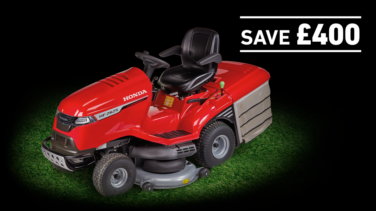 Honda tractor on grass in a dark background with save £400