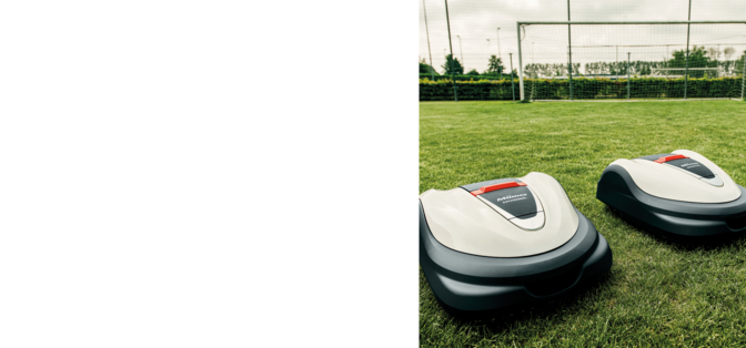 side angled view of honda miimo robot lawnmower mowing a football pitch