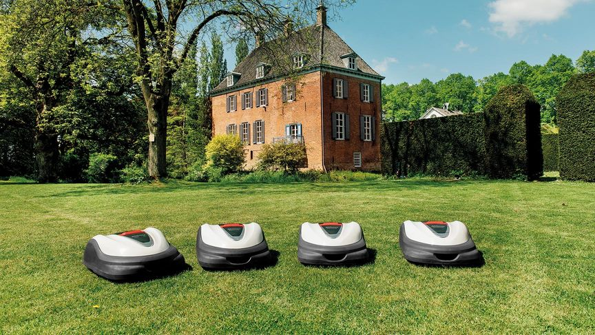 front view of team of honda miimo robotic lawnmowers on a lawn in the garden