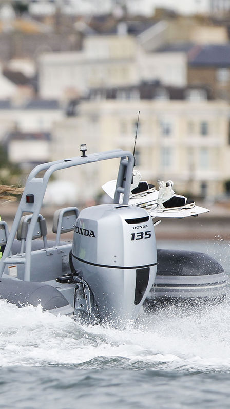 Boat using Honda engine, being used by model, coastal location.